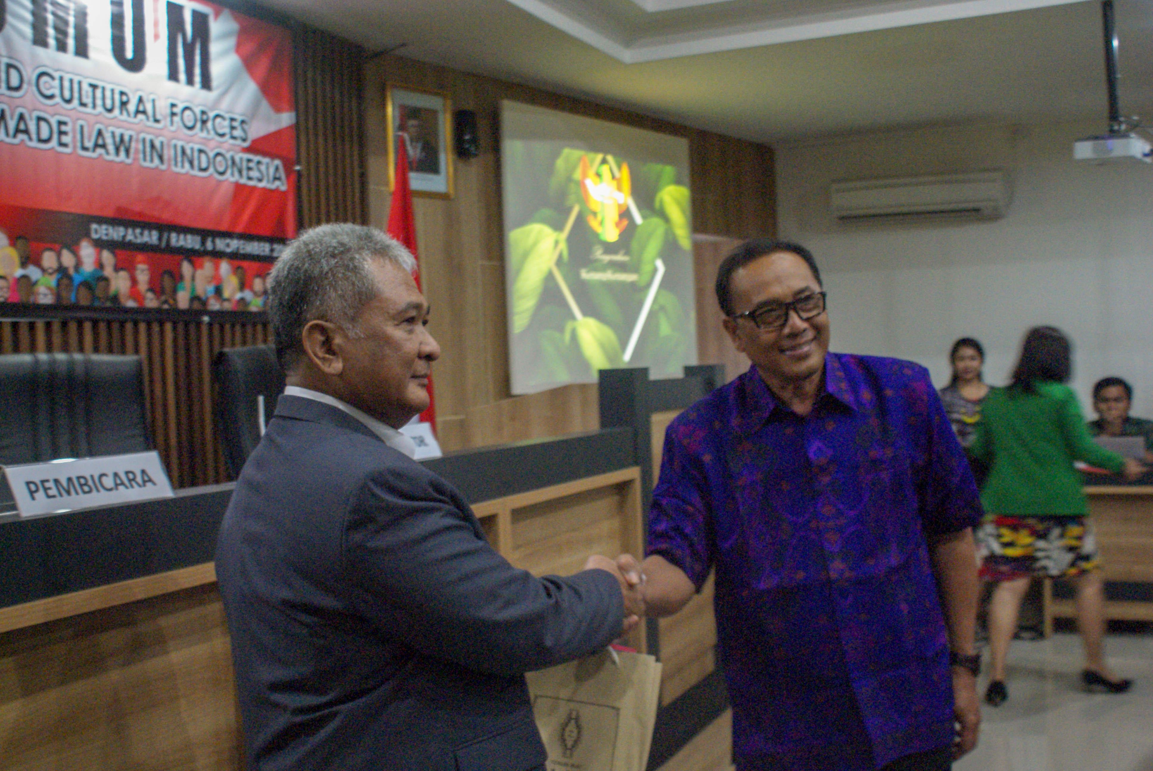 Profesor Ade saptomo menerima kenang-kenangan dari Dekan Fakultas Hukum Universitas Warmadewa